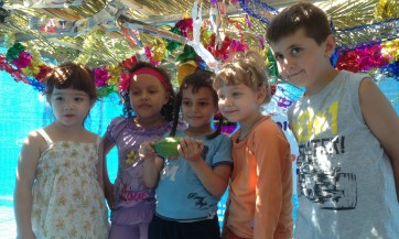 Maria (age 5) of Ukraine, Gavriel (age 5) of Yemen, Annamalai (age 5) of Peru, AJ (age 6) of South Africa, and Sofia (age 4) of Argentina—all of them recent immigrants to Israel—pose in the sukkah they helped build at The Jewish Agency's Ye'elim Immigrant