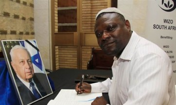 At the Ariel Sharon Memorial, Raphel Kitiaka from Africa Bless Israel signs the condolenses book.